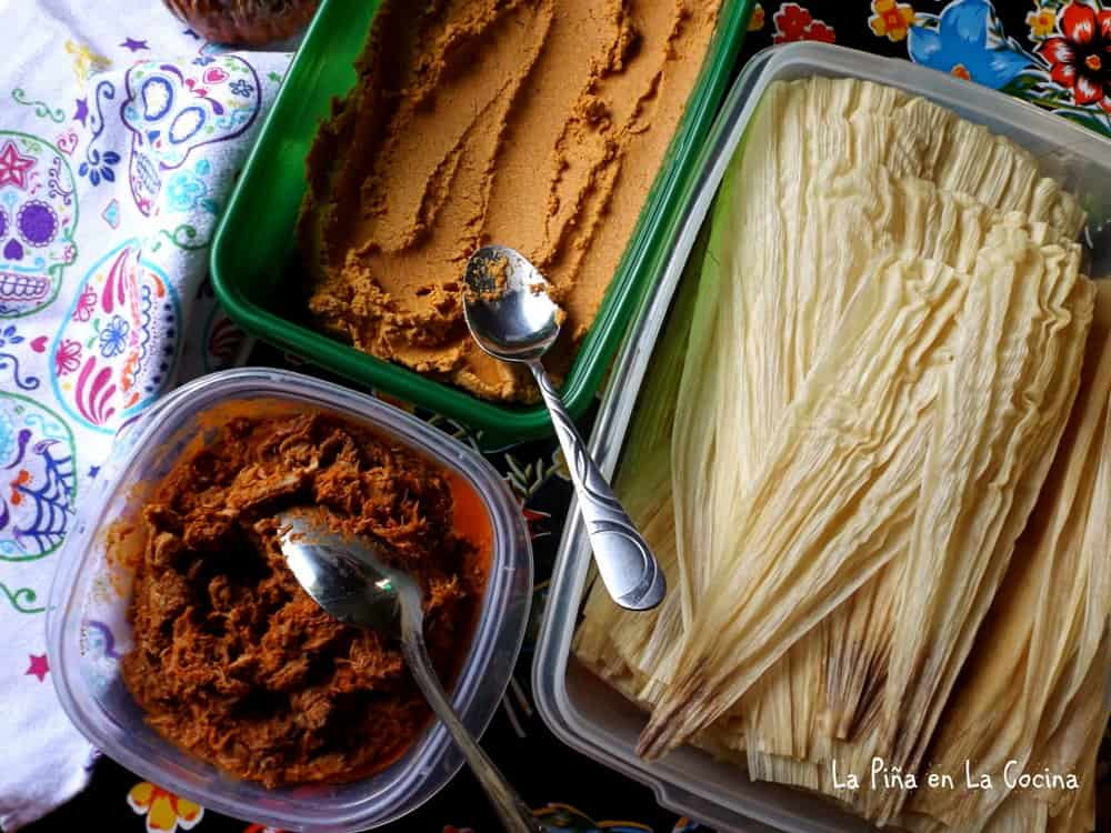 Top view of tamal ingredients, corn husk, masa and meat filling