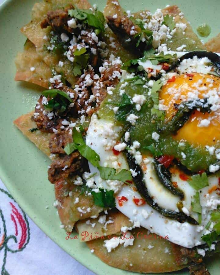 Chilaquiles Verdes with Carne Guisada, Poblano, Cotija Cheese and Sunny Side Up Egg