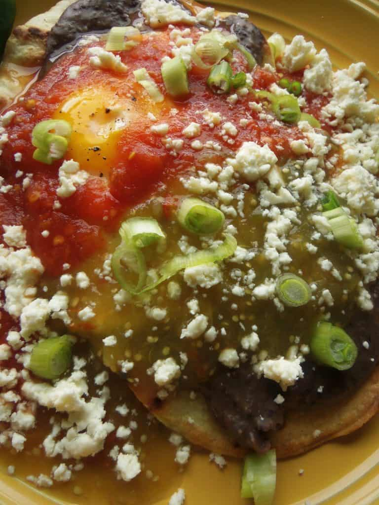 Huevos Divorciados, Crispy Tostada, Creamy Black Bean, Sunny Side Eggs, Salsa Roja, Salsa Verde, Cotija Cheese and Green Onions