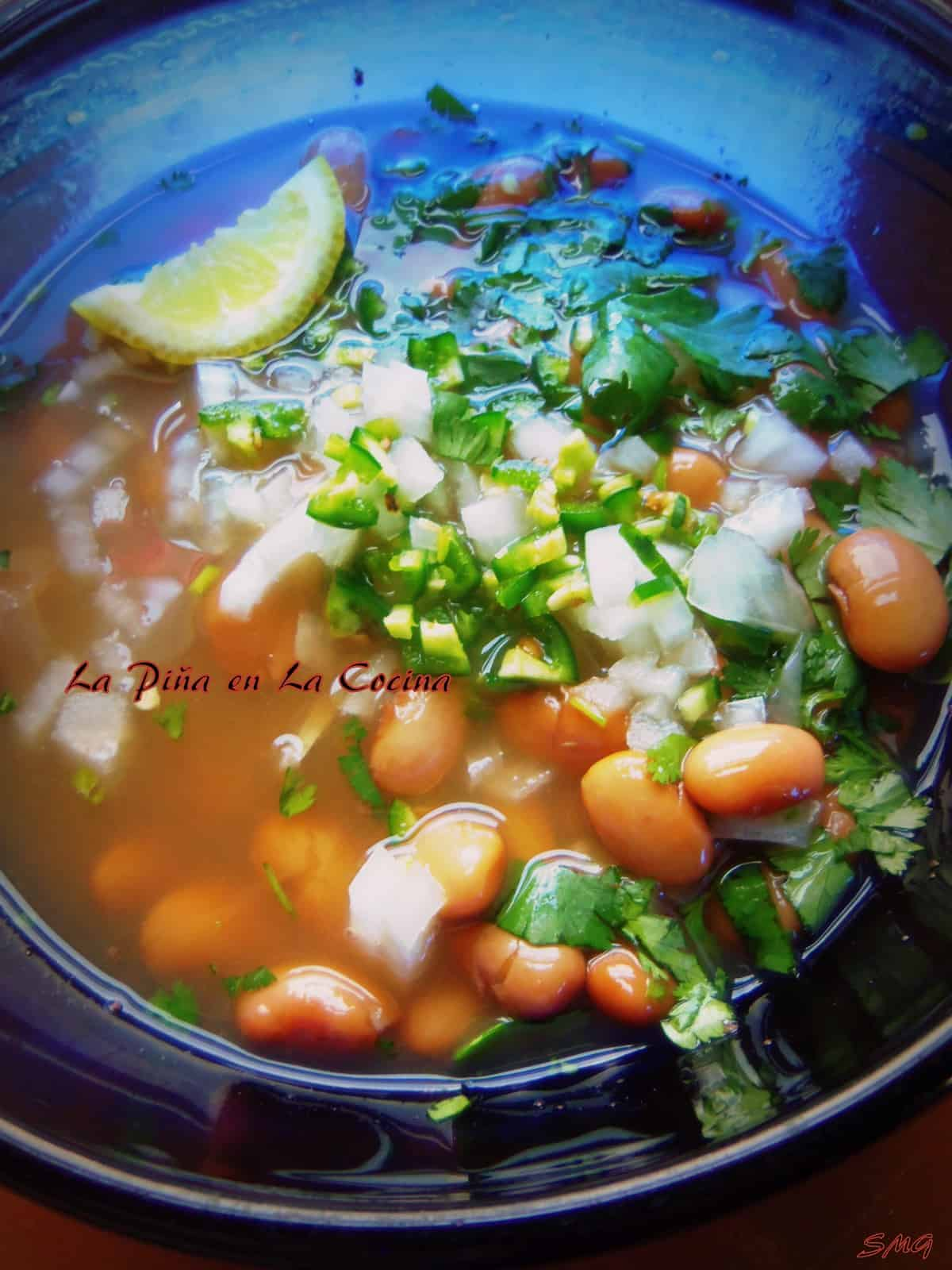 My favorite way to enjoy Frijoles de Olla is in their own broth with diced onion, chile, cilantro and lemon