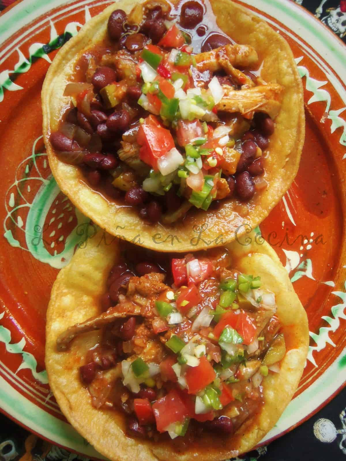 Tinga de Pollo served on tostadas with red beans and pico de gallo