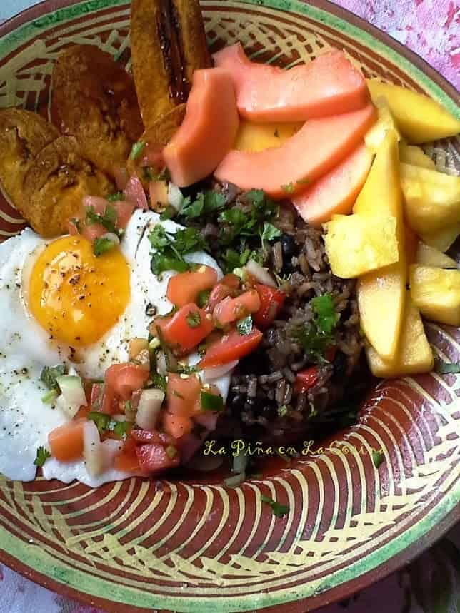 A typical breakfast in Costa Rica. Gallo Pinto Beans and Rice with and Egg, Plantains, Fresh Fruit, Salsa Lizano  and Sometimes a Fresh Salsa