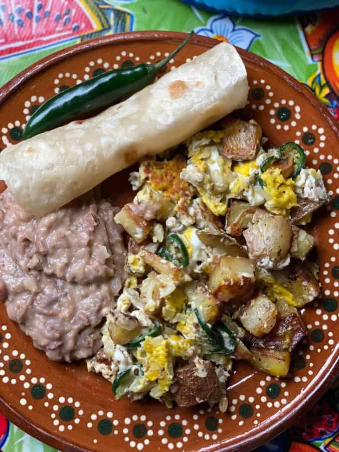 Potato and egg scrable with beans and flour tortilla plated