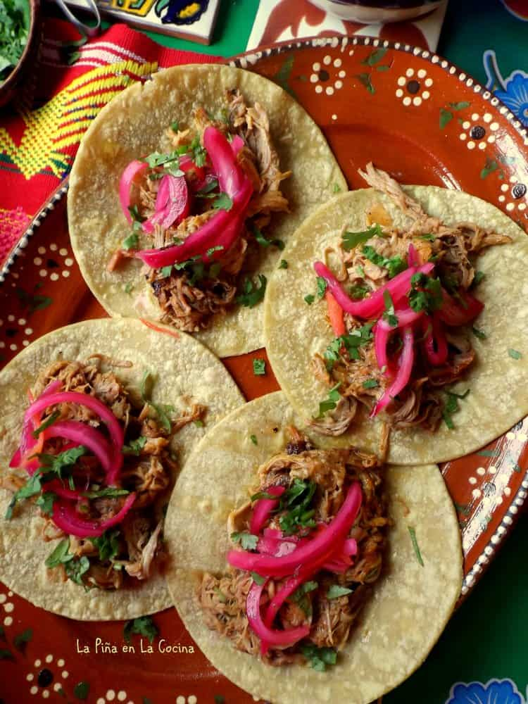 Pork pibil tacos on yellow corn tortillas with pickled red onions, salsa and cilantro