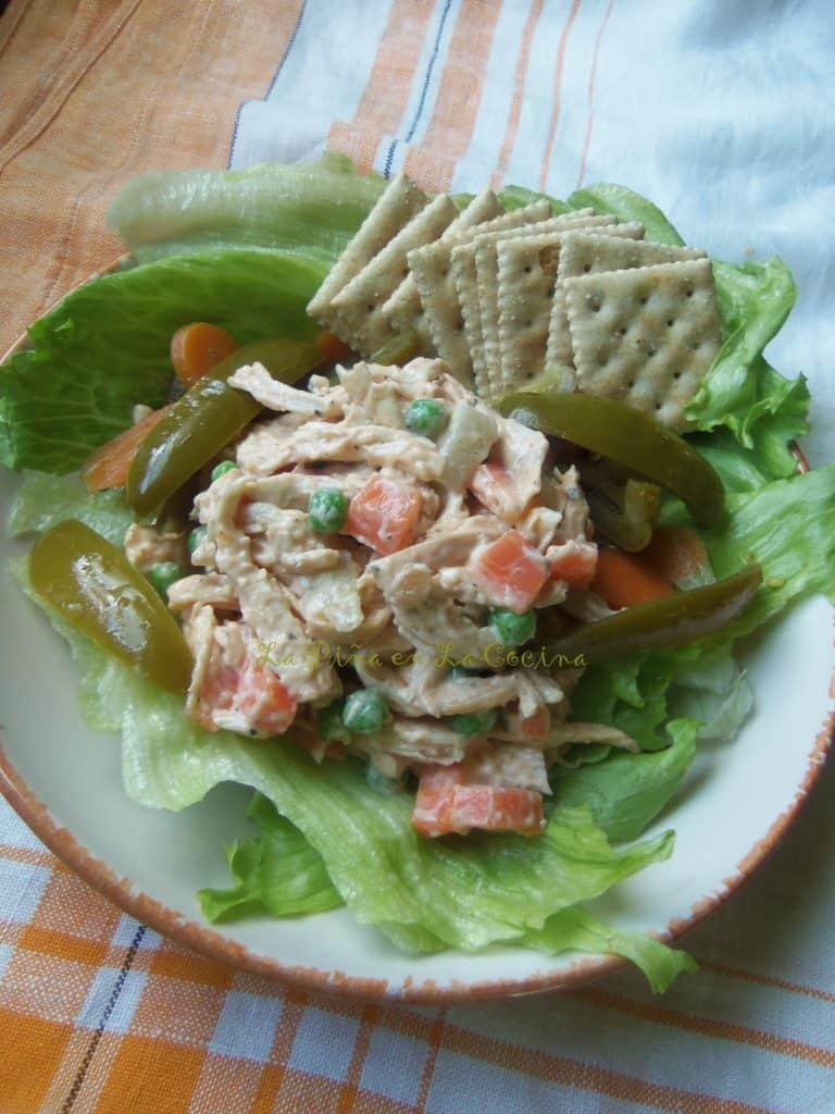 Ensalada de Pollo, chicken salad on top of lettuce leaves in a shallow bowl with crackers