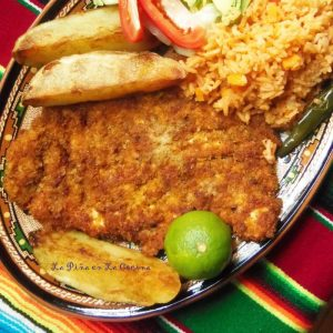 Chicken Milanesa on a plate with potato wedges and rice