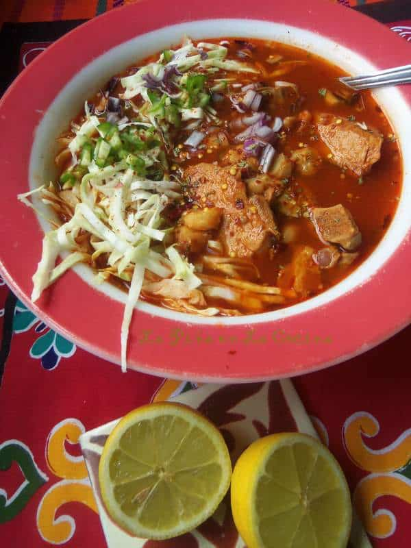 Pozole in a large bowl with lemons on the side