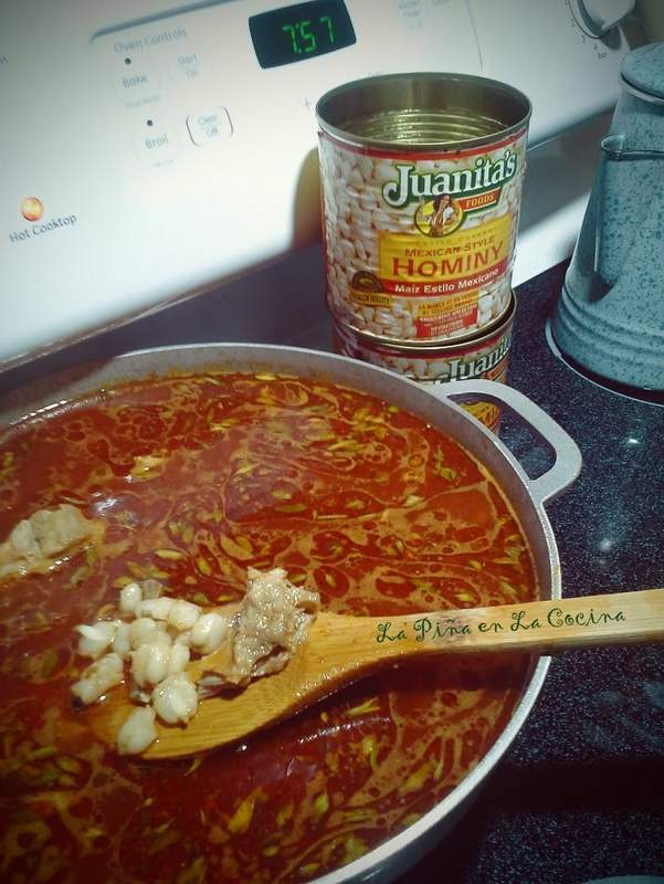 Red Chile Pork Pozole cooking in large pot, empty cans of hominy
