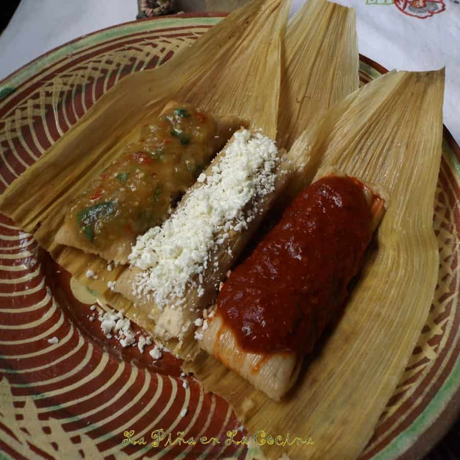 Three Fresh Corn Tamales With Jalapeño and Cheese, garnished with different toppings