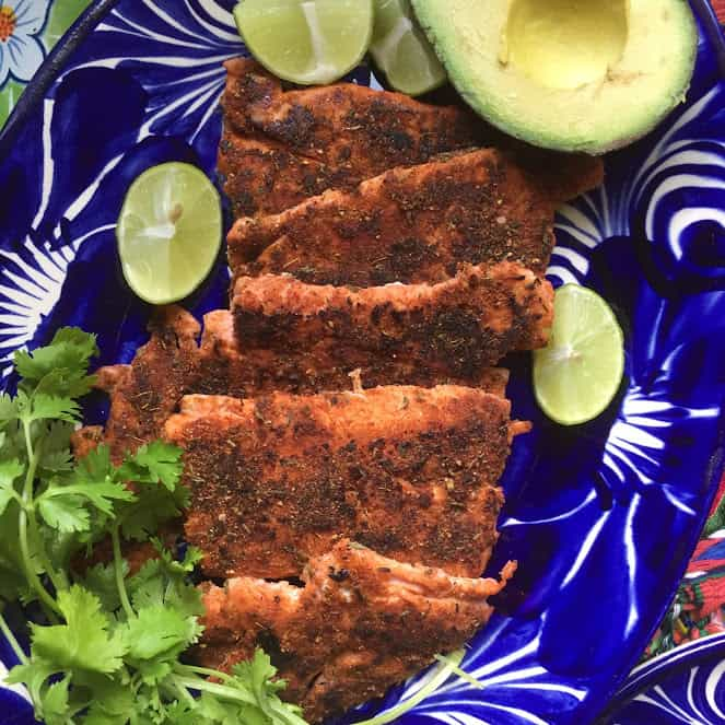 Blackened Salmon on a plate with lime, cilantro and avocado