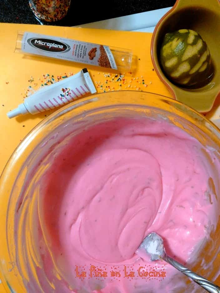 Pink frosting mixed in a bowl with lime zest, colr gel and lime on the side