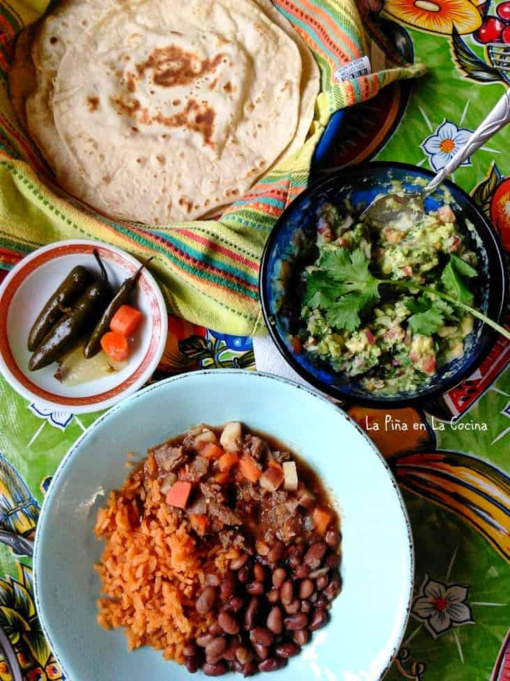 Carne Picada Con Verduras plated with rice and beans, bowl of guacamole, flour tortillas and pickled serranos