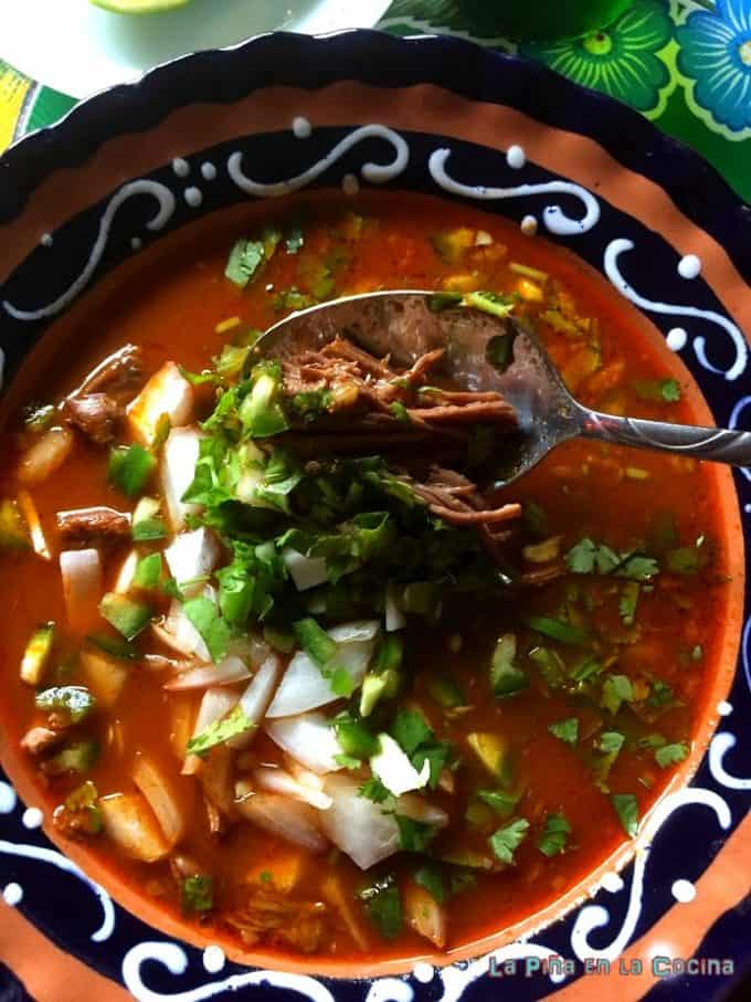 Birria in bowl with garnishes and spoon #birriaderes #beefbirria
