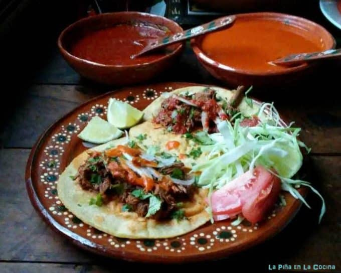 Birria tacos with spicy salsa on the side
