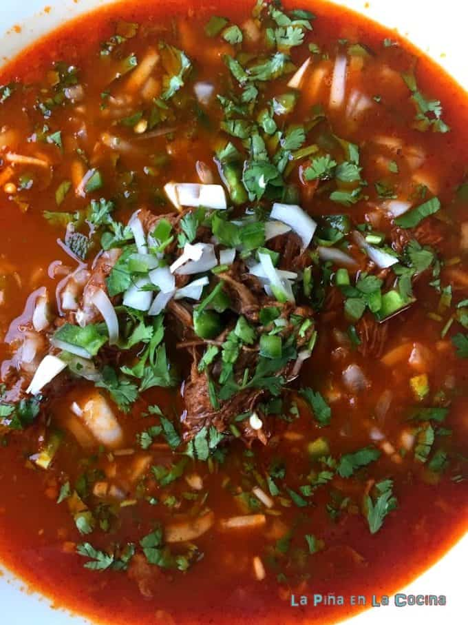 Birria in bowl with fresh garnish top view