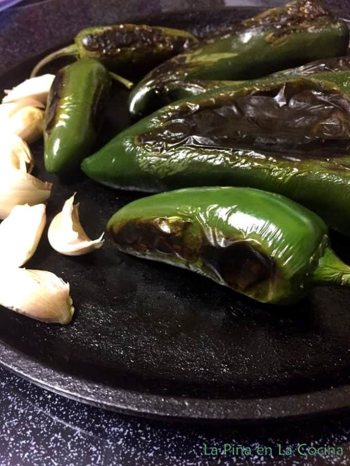 Green chiles and garlic roasting on griddle