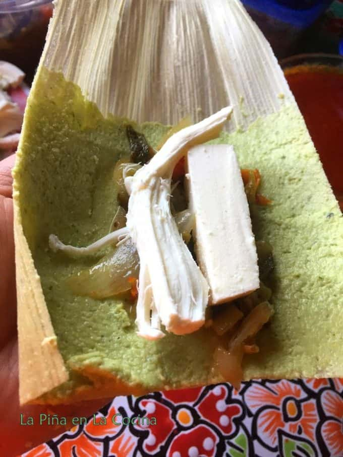 Open, uncooked tamal with masa and filling