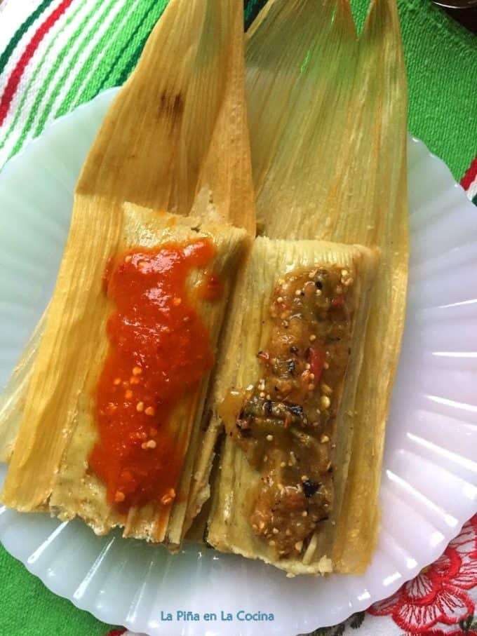 Green chile tamales plated with salsa garnish close up