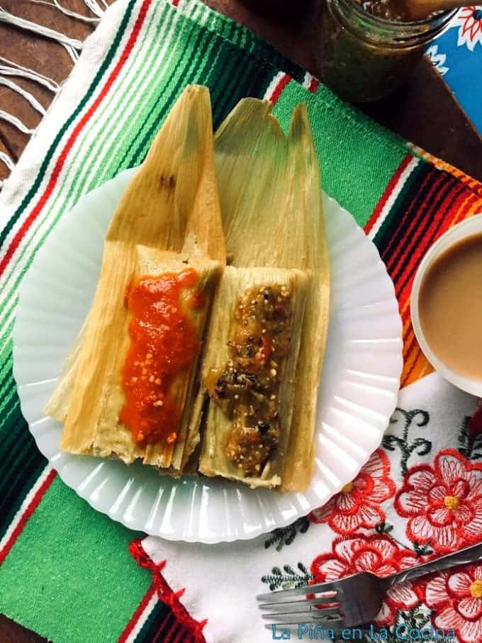 Tamales verdes plated and garnished with red and green salsas