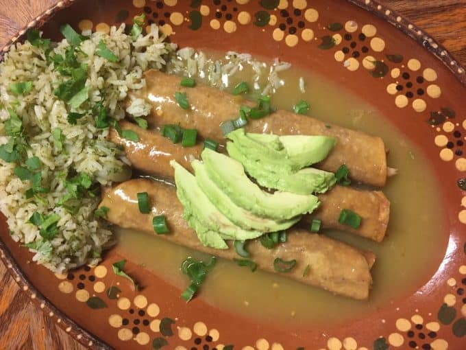 Cilantro rice served with chicken taquitos in salsa verde plated