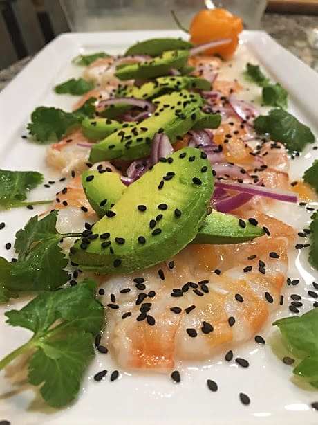 Coconut Habanero Shrimp Aguachiles Plated with Avocado, Black Sesame Seeds and Cilantro