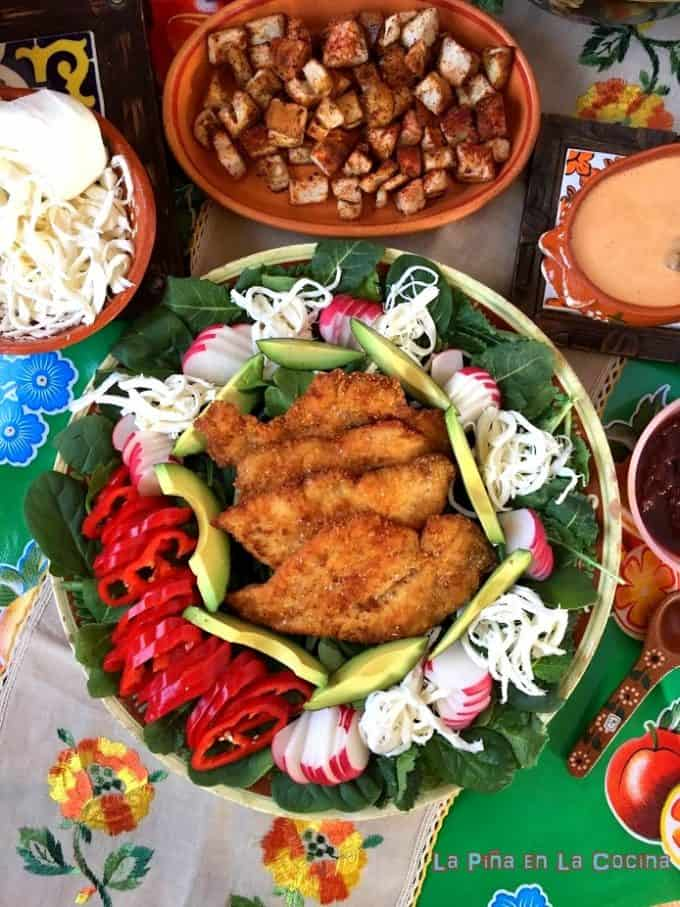 Chicken Milanesa Salad on a Platter with dreesing, croutons and cheese
