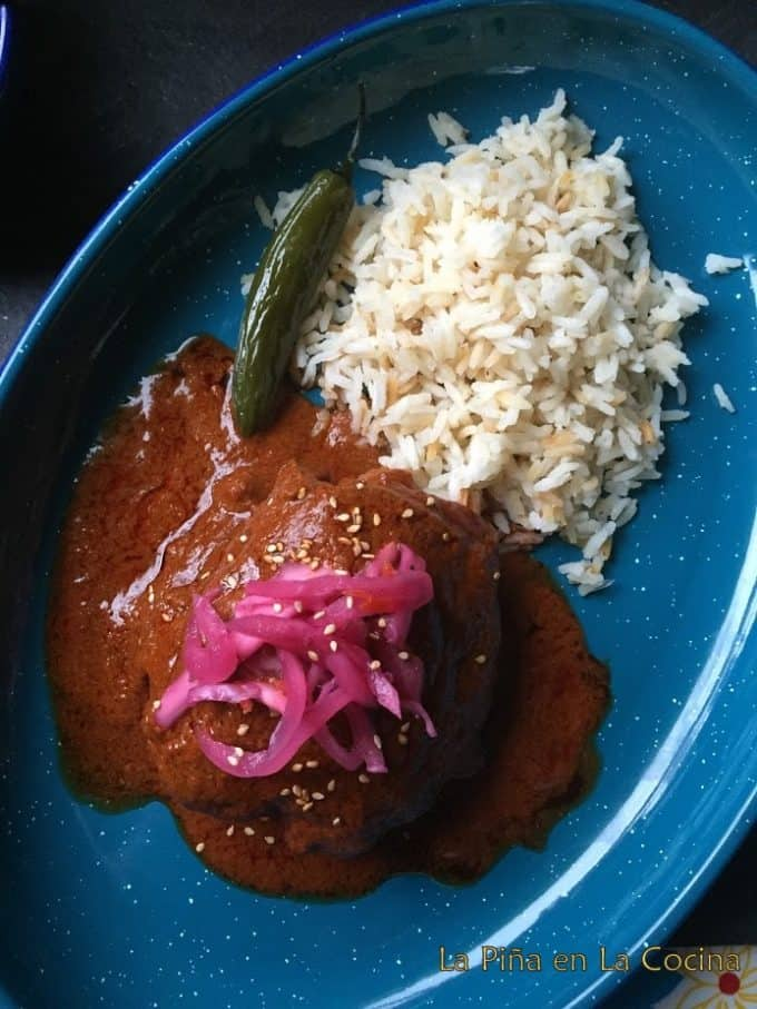 Red Chicken Pipian Plated with a side of white rice and chile serrano