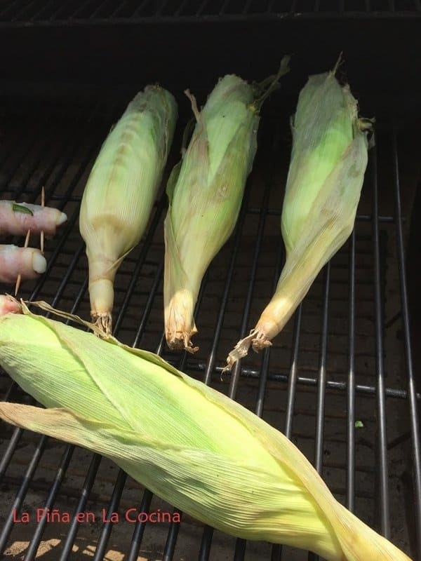 Fresh corn with husk on on the indirect side of a charcoal grill