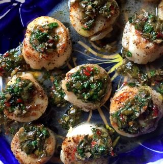 Seared Scallops on a platter garnished with chimichurria