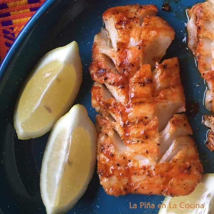 Stove top grilled cod plated with lemon wedges