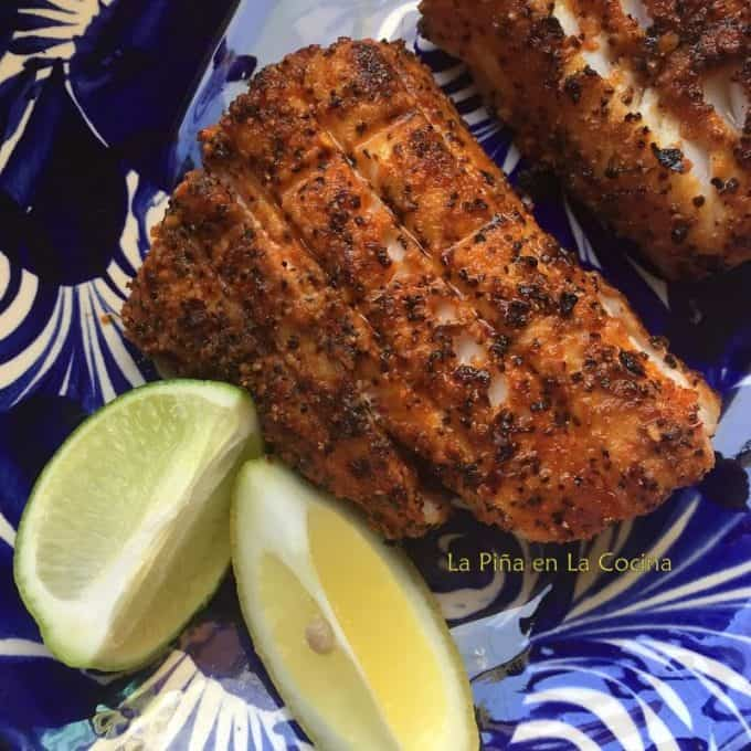 Grilled black cod close up on plate with lemon wedges