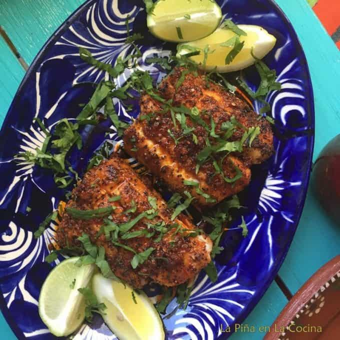 Grilled Black Cod Plated with lemon wedges and cilantro