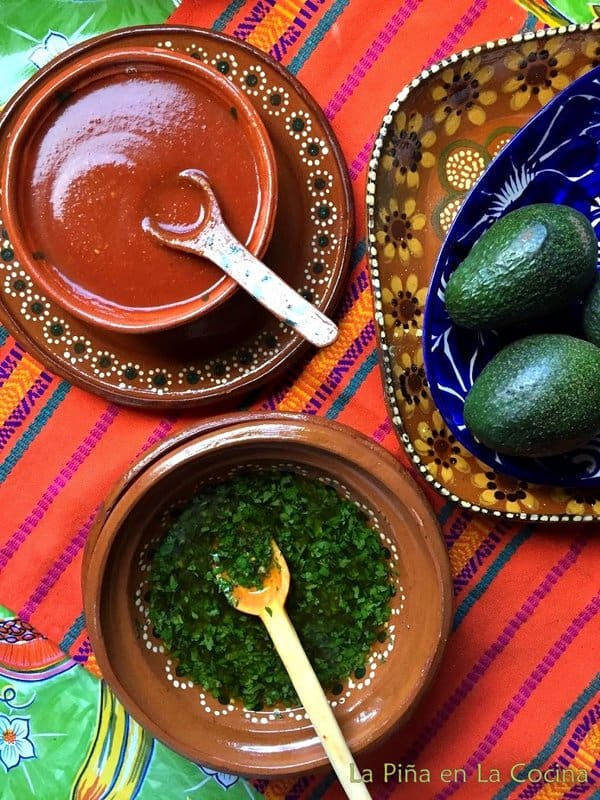 Bowl of chile de arbol salsa, bowl of mojo sauce and avocados
