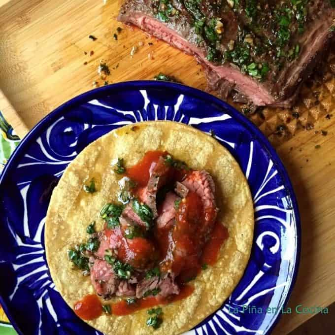 Grilled Flank Steak Taco On a Plate Garnished with Red Salsa