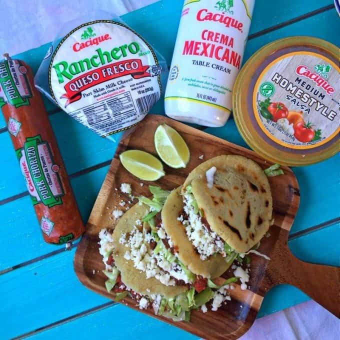 Three stuffed gorditas on wooden plate. Packaged Cacique products shown in full packages