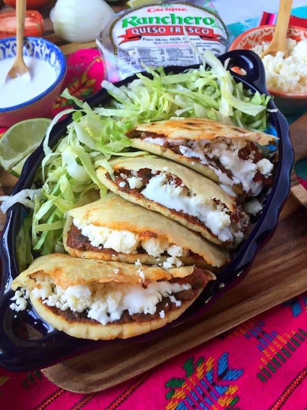 Four stuffed gorditas with lettuce on the side