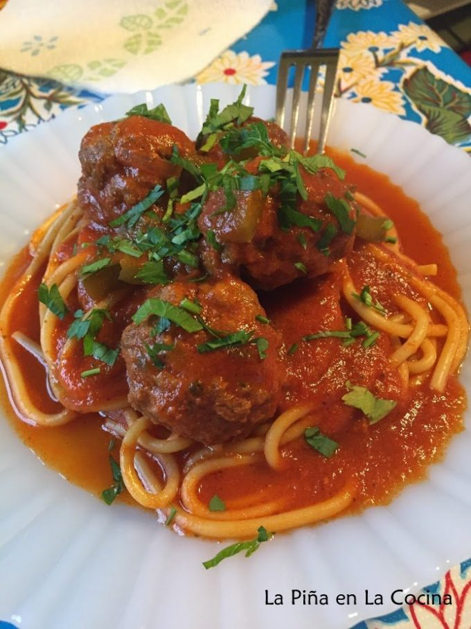 Spaghetti and meatballs with cilantro garnish , plated close up