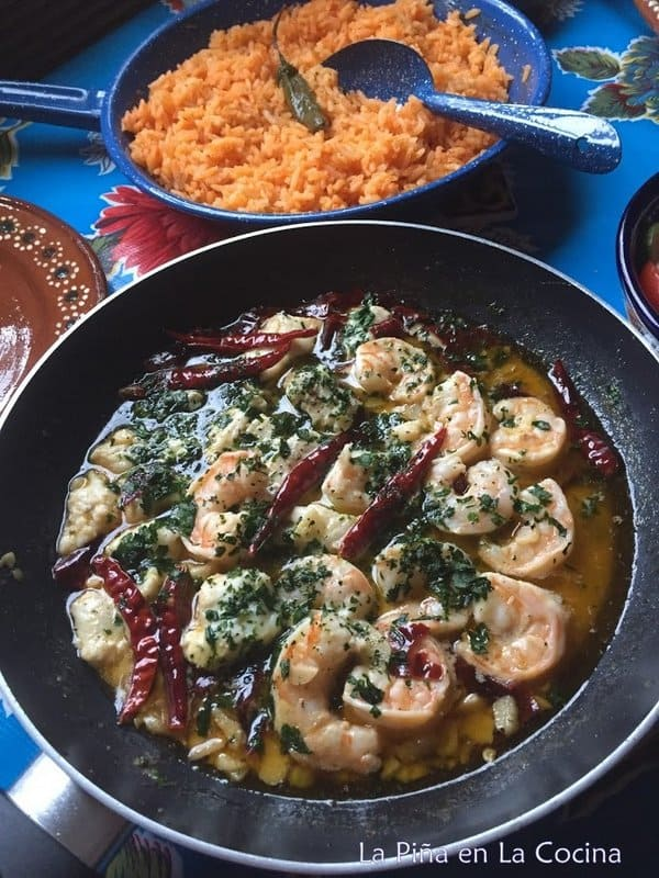 Skillet of Mexican garlic shrimp and skillet of rice on the table