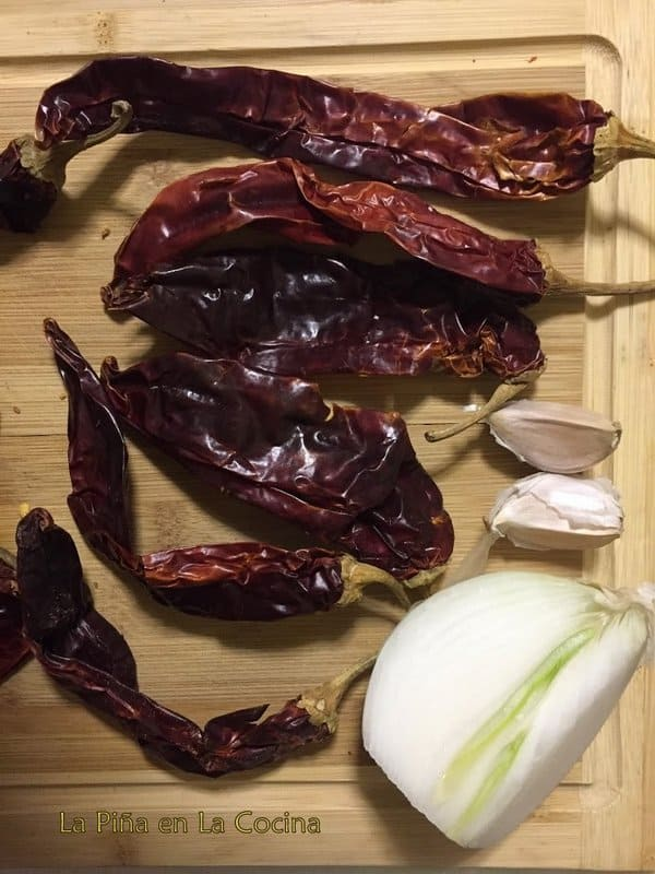 Dried  guajillo chiles with piece of onion and 2 cloves of garlic on board
