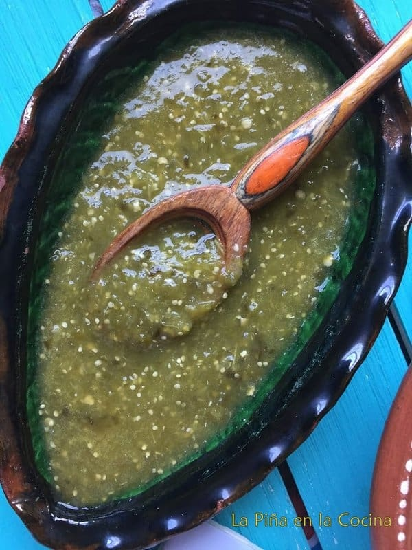 Salsa verde in a serving dish with wooden spoon
