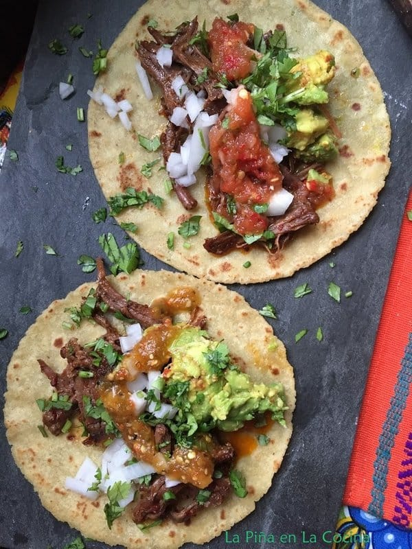 Two barbacoa tacos garnished with guacamole, salsa, cilantro, onion, lime