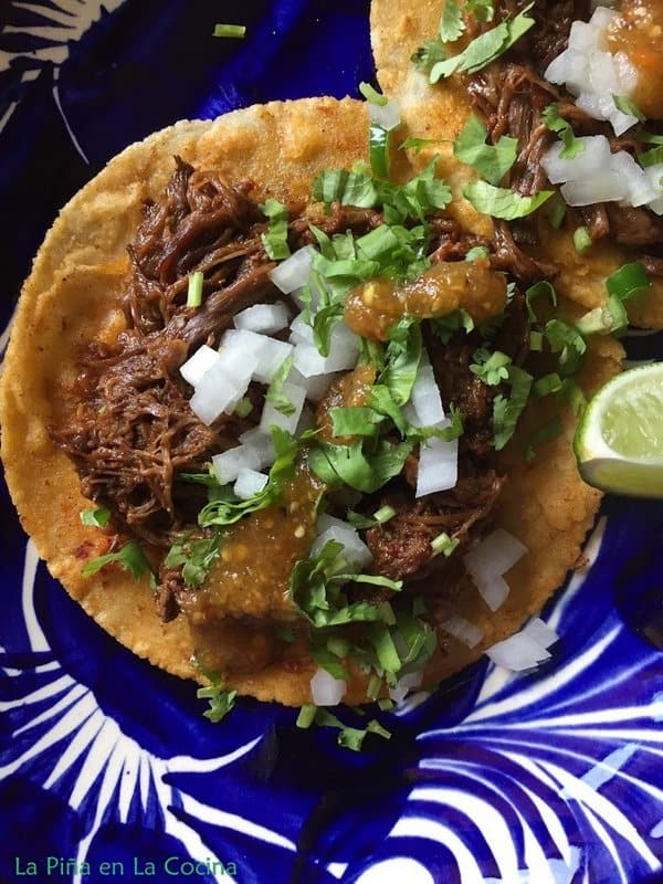 Barbacoa taco garnished with fresh topping on a blue Mexican plate