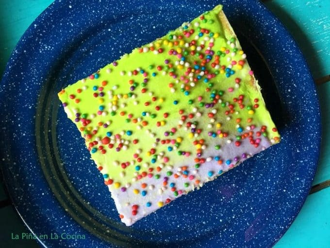 Big piece of cake with purple and green frosting, sprinkles