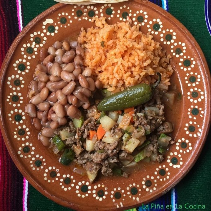Top view of plated picadillo with rice and beans on Mexican plate