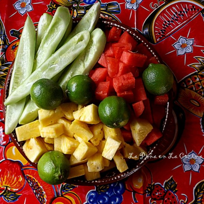Fresh pineapple, watermelon, cucumber with uncut limes on a plate.