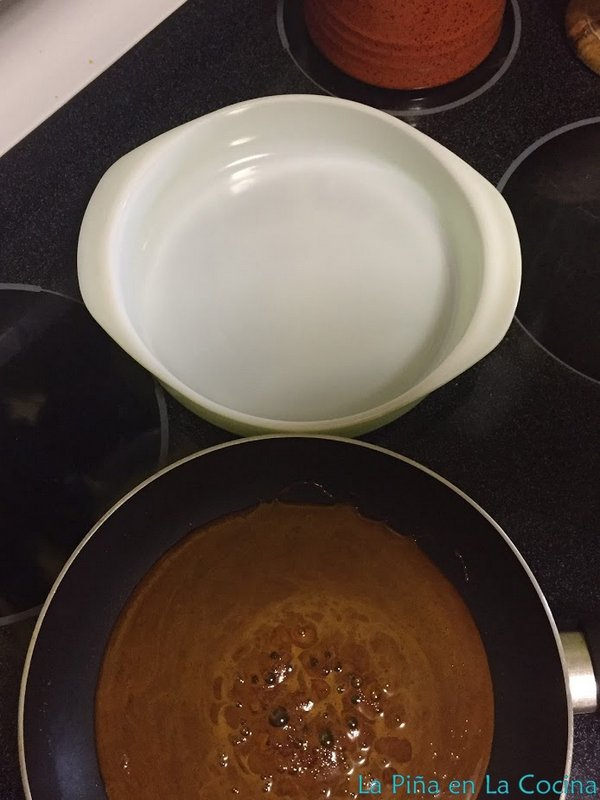 Hot caramel sauce in the skillet with waiting pan next to it