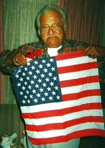 My dad, Ramiro, holding a bandana that resembles the American flag.