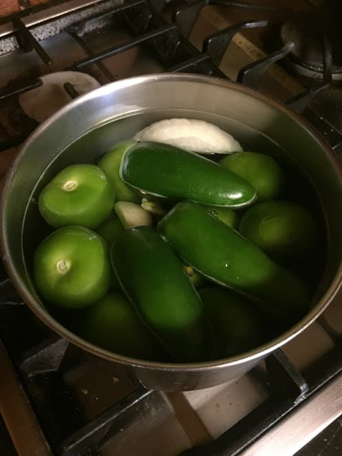 Salsa verde ingredients in pot with water