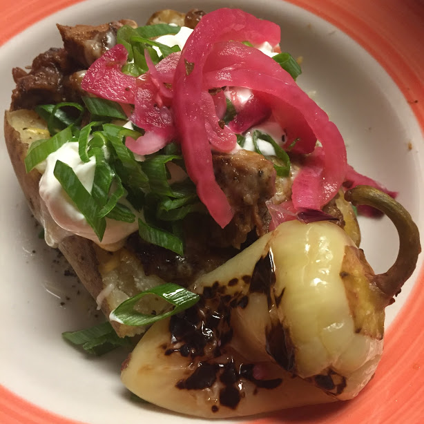 A loaded beef baked potato with pickled red onions and a pickled chile guero