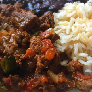 spicy marinated beef with rice and beans plated up close
